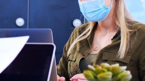 Young-Woman-in-Face-Mask-Typing-On-Laptop-In-Modern-Office