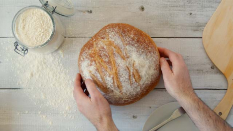Top-View-Hands-Placing-Fresh-Bread-on-Table