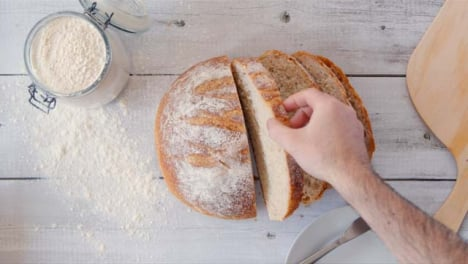 Top-View-Hand-Picking-Up-Slice-of-Fresh-Bread
