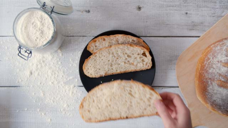 Top-View-Hand-Taking-Slice-of-Bread-from-Plate