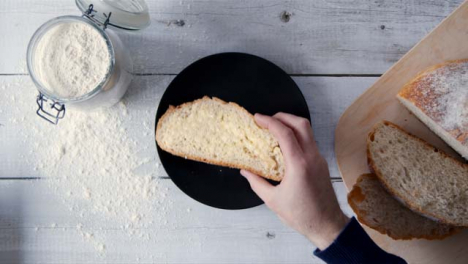 Top-View-Hand-Taking-Slice-of-Buttered-Bread-from-Plate