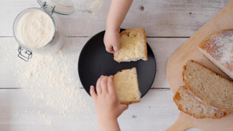 Two-View-Two-Kids-Take-a-Slice-of-Bread-from-Plate