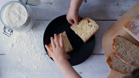 Two-View-Children-Take-a-Slice-of-Bread-from-Plate