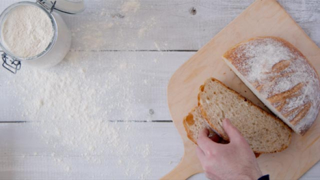 Top-View-Hand-Picking-Up-Bread-Slice-from-Peel