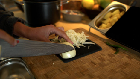 Dolly-Out-Shot-of-Female-Hands-Slicing-a-White-Onion