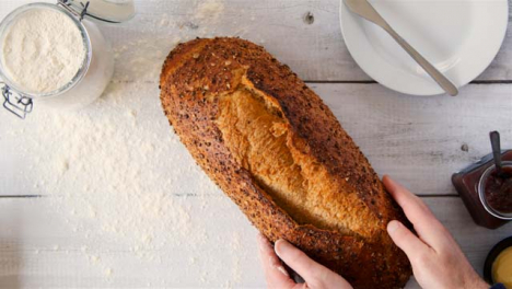 Top-View-Hands-Pick-Up-Seeded-Bread-on-Table
