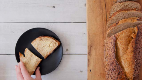 Top-View-Hand-Takes-Slice-of-Buttered-Seeded-Bread-from-Plate