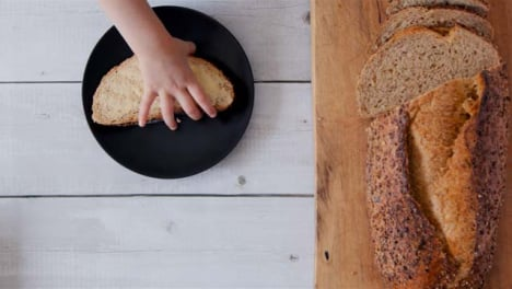 Top-View-Child-Picking-Up-Buttered-Slice-of-Bread