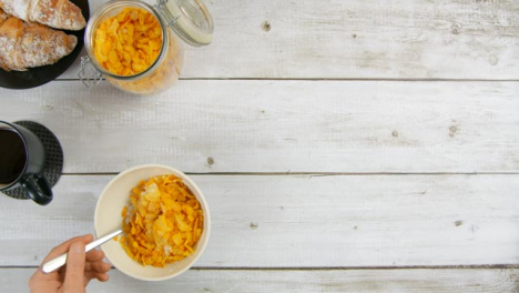 Top-View-Eating-Corn-Flakes-from-Bowl-at-Breakfast