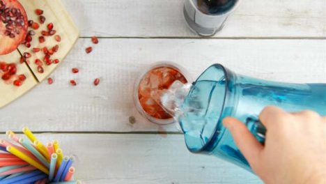 Top-View-Male-Hands-Adding-Water-and-Pomegranate-Seeds-to-Drink