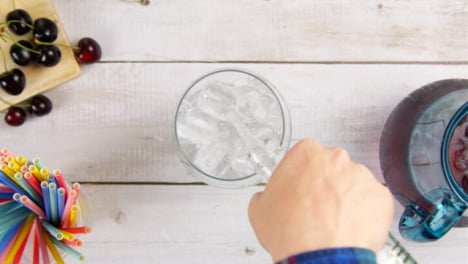 Top-View-Male-Hands-Pouring-Ice-and-Spirit-into-a-Glass