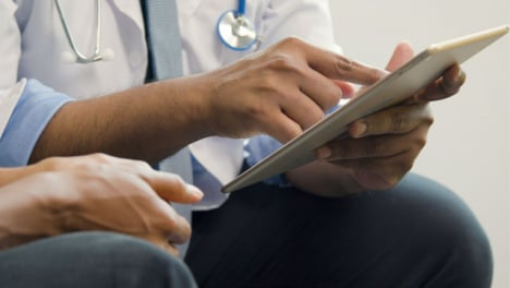 Doctor-Using-Tablet-Whilst-Talking-to-Patient