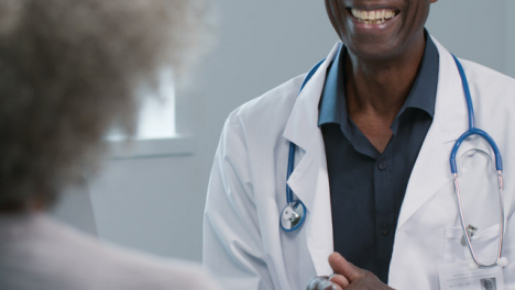 Mid-Section-Smiling-Doctor-Talking-to-Patient