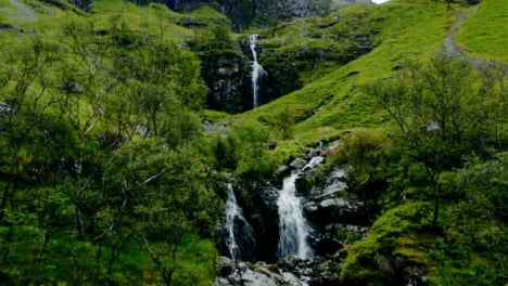 Aerial-Drone-Shot-of-Downhill-Stream-and-Waterfall-in-Glen-Coe