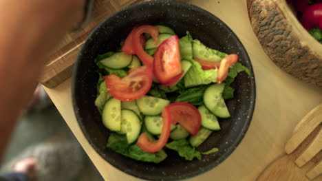 Close-Up-of-Female-Hands-Adding-Sliced-Tomato-to-Salad-Bowl