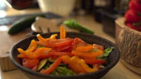 Close-Up-of-Female-Hands-Adding-Sliced-Pepper-to-Salad-Bowl