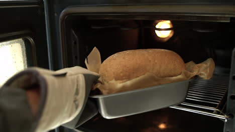 POV-of-Female-Hands-Taking-Freshly-Baked-Bread-Out-of-Oven