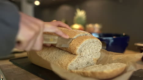 Close-Up-of-Female-Hands-Slicing-Loaf-of-Bread-