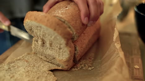 Extreme-Close-Up-of-Female-Hands-Slicing-Loaf-of-Bread-