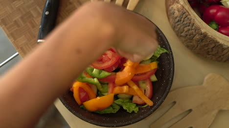 Close-Up-of-Female-Hands-Placing-Green-Pepper-In-Salad-Bowl