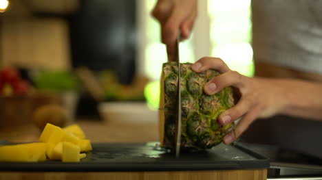 Close-Up-of-Female-Hands-Cutting-a-Slice-of-Pineapple-