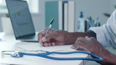 Doctor-s-Hands-at-Desk-Typing-and-Writing-Notes