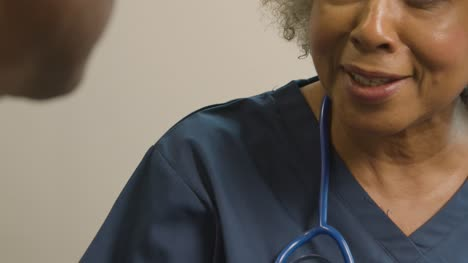 Close-Up-Smiling-Middle-Aged-Doctor-Talking-to-Patient