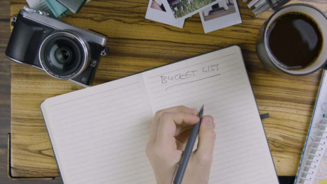 Man-Writing-Bucket-List-In-Notebook-on-Coffee-Table