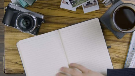 Man-Sipping-Coffee-and-Turning-Page-In-Notebook