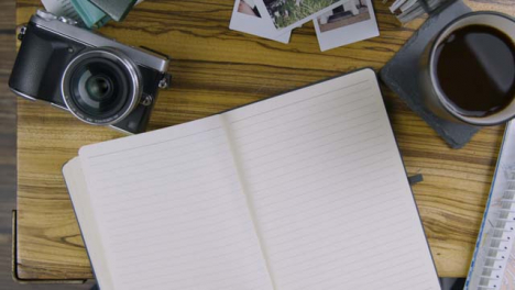 Man-Turning-Blank-Page-In-Notebook-On-Coffee-Table
