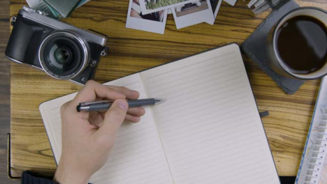 Man-Tapping-Pen-On-Blank-Page-of-Notebook-On-Coffee-Table