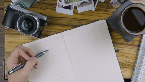 Man-Tapping-His-Pen-On-Blank-Page-of-Notebook-On-Coffee-Table