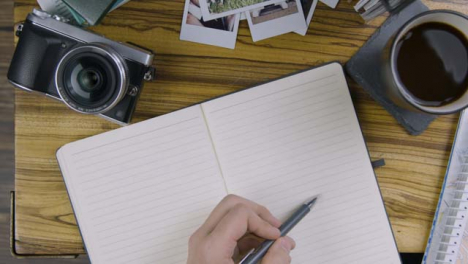 Man-Tapping-His-Pen-On-Blank-Notebook-Page-On-Coffee-Table