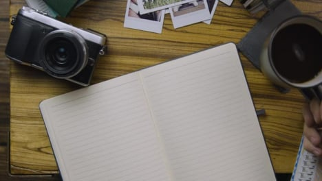 Man-Sipping-Coffee-and-Turning-Page-In-His-Notebook
