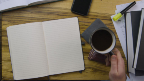 Man-Placing-Pen-On-Blank-Notebook-Page-Whilst-Sipping-Coffee