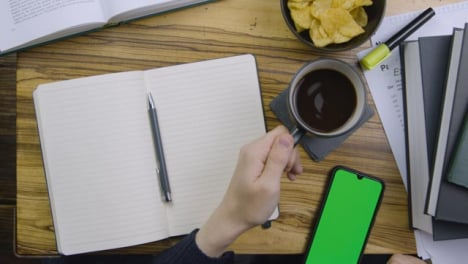 Man-Placing-Coffee-Down-and-Scrolling-On-Smart-Teléfono-with-Green-Screen