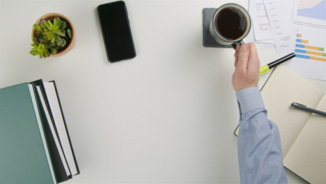 Businessman-Taking-a-Sip-of-Coffee-Before-Placing-It-Back-Down