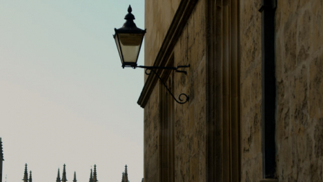 Rising-Shot-of-Old-Wall-Mounted-Light-On-University-of-Oxford-Grounds