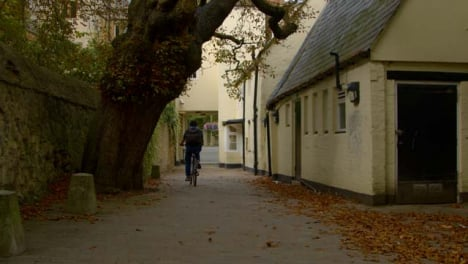 Rising-Shot-of-Cyclist-Riding-Through-Scenic-Alleyway-In-Oxford