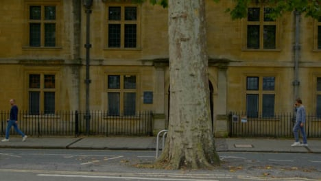Wide-Shot-of-People-Walking-Past-Old-College-In-Oxford