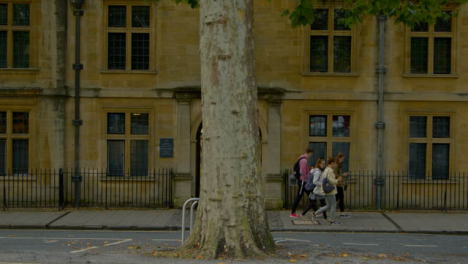 Wide-Shot-of-People-Walking-Past-Old-College-In-Oxford-England