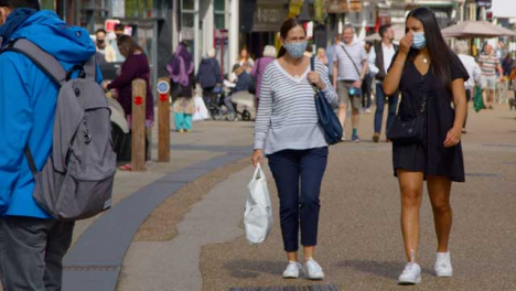 Two-Women-In-face-Masks-Walking-Down-Busy-Cornmarket-Street-In-Oxford