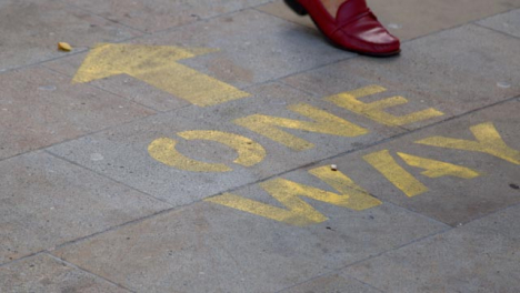Close-Up-Shot-of-Feet-Walking-Over-One-Way-Pavement-Marking