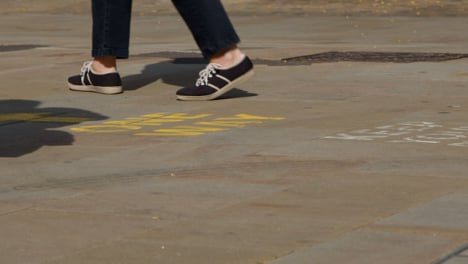 Close-Up-Shot-of-Feet-Walking-Over-One-Way-Pavement-Marking-In-Oxford