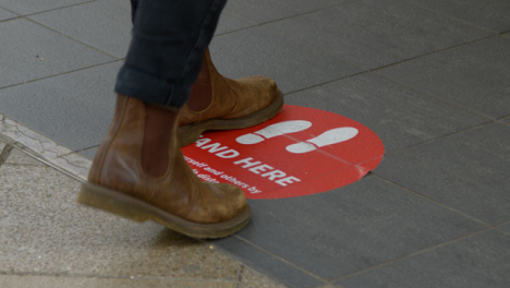 Close-Up-Shot-of-Feet-Standing-On-Stand-Here-Floor-Sign