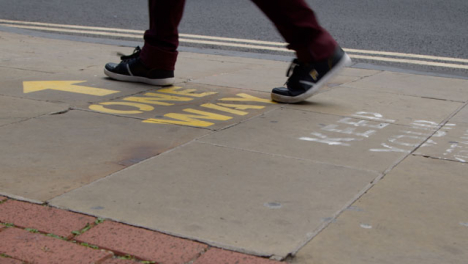 Close-Up-Shot-of-Pedestrians-Feet-Walking-Over-One-Way-Pavement-Marking-In-Oxford