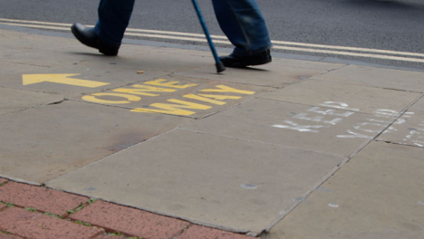 Close-Up-Shot-of-Pedestrians-Feet-Walking-Over-One-Way-Pavement-Marking-In-Oxford-England