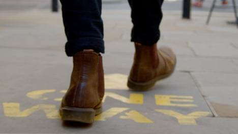 Tracking-Shot-of-Feet-Walking-Over-One-Way-Floor-Marking-In-Oxford-