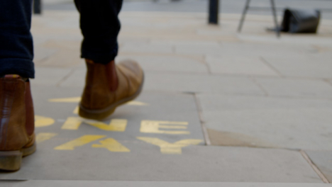 Tracking-Shot-of-Feet-Walking-Over-One-Way-Floor-Marking-In-Oxford-England