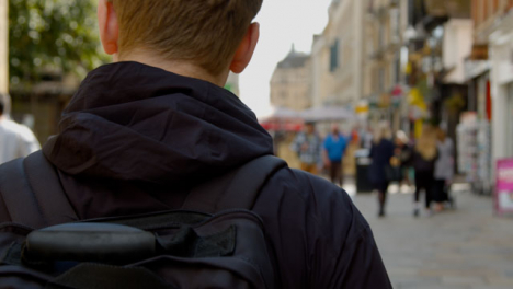 Over-the-Shoulder-Shot-of-Man-Walking-Down-Cornmarket-Street-In-Oxford